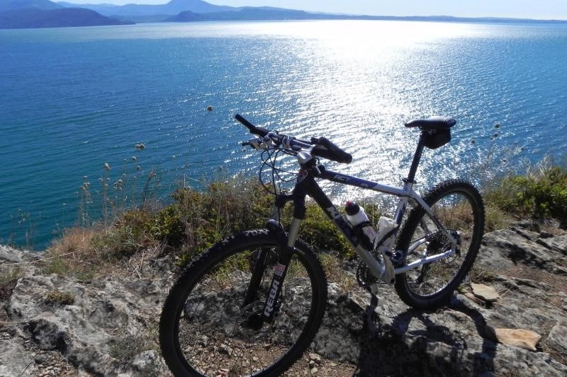 A mountain bike sits beside the shimmering waters of lake garda