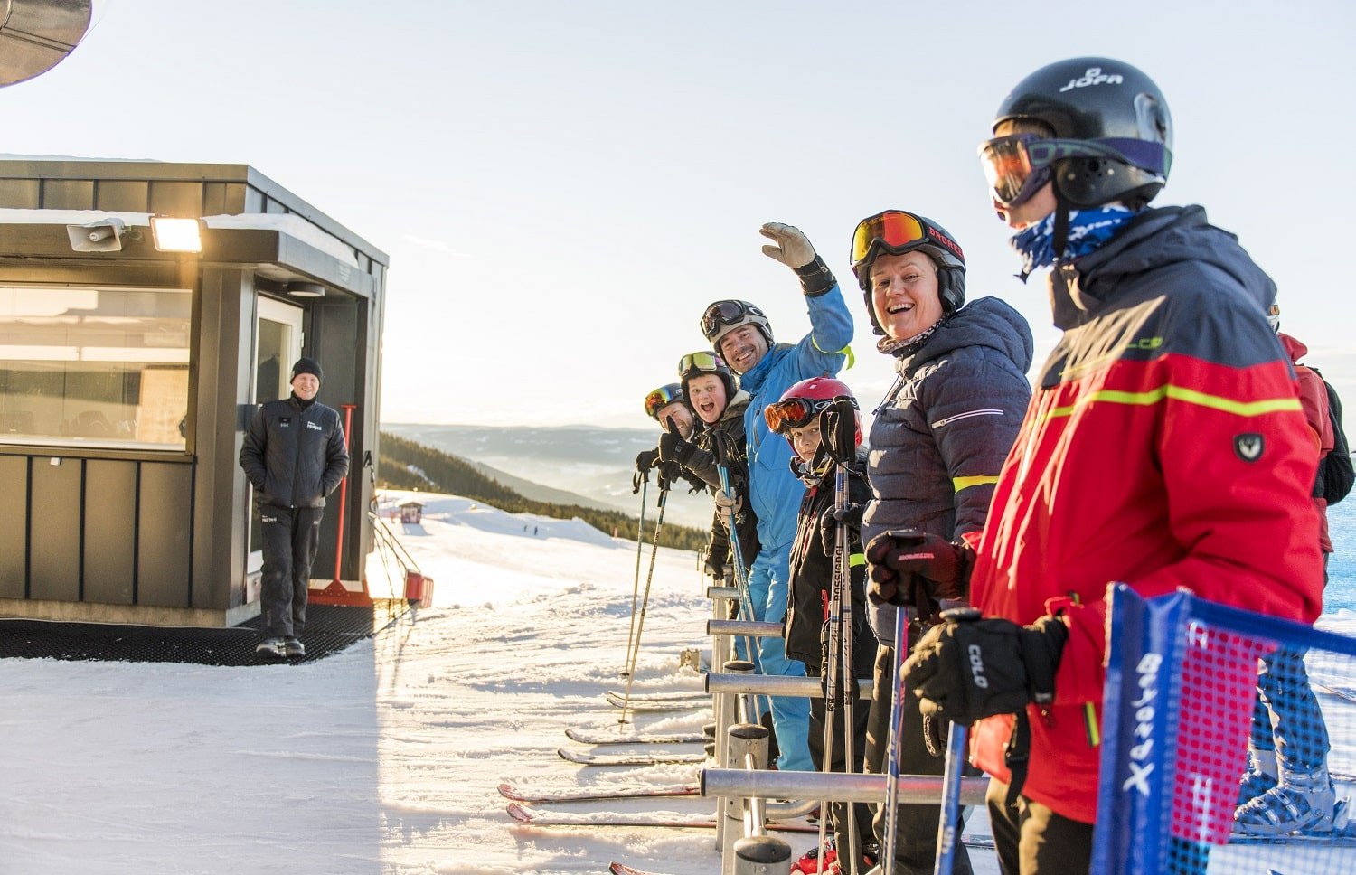 people queuing at ski lift and waving